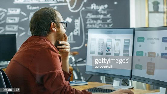 Male Mobile Video Game Application Developer Works on a Personal Computer, Designing Wireframe, He's Smooths the Beard in Thinking Gesture. He Works in the Creative Indie Studio. : Stock Photo