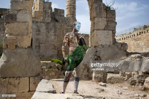 A male model poses after being painted by Israeli artist Avi Ram from Airbrush Hero at the Tower of David Museum on April 27 2017 in Jerusalem Israel
