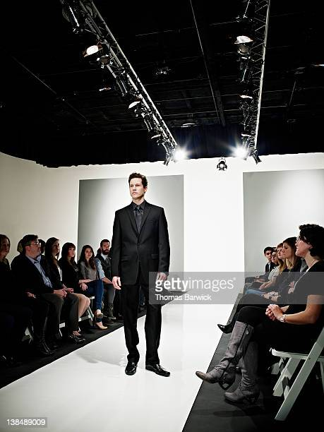 Male model wearing business suit on catwalk