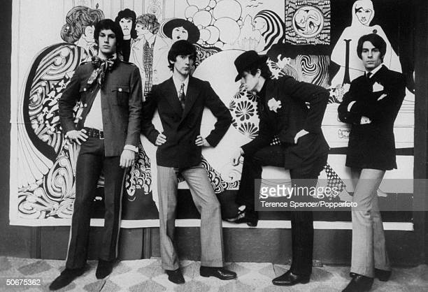 Male models including Ossie Clark and Niel Winterbottom posing in front of the blowup of Albert Little's etching in the Hung On You boutique Chelsea...