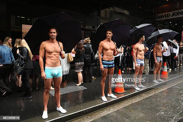 Male models pose with umbrellas prior to Heidi Klum's launch of her Intimates Collection at David Jones Elizabeth Street Store on January 28 2015 in...