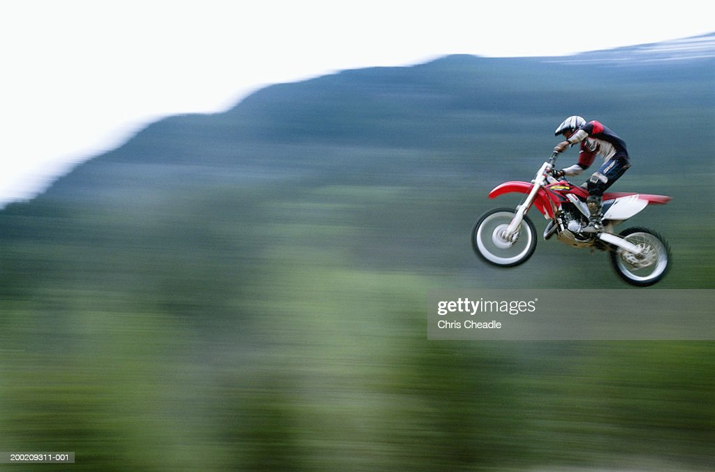 Male motocross biker jumping in air (blurred motion)
