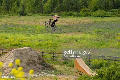 A male mountain bike rider does a no hander trick off a big jump in the summertime. : Stock-Foto