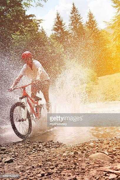 Male mountain biker crossing creek.