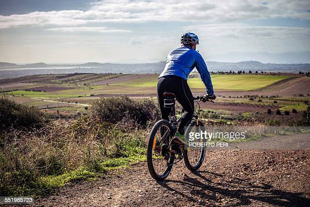 Male mountain biker cycling down dirt track, Cagliari, Sardinia, Italy