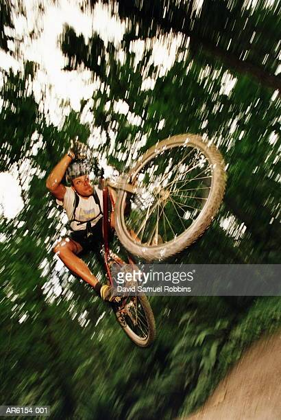 Male mountain biker in mid jump, low angle view (blurred motion)