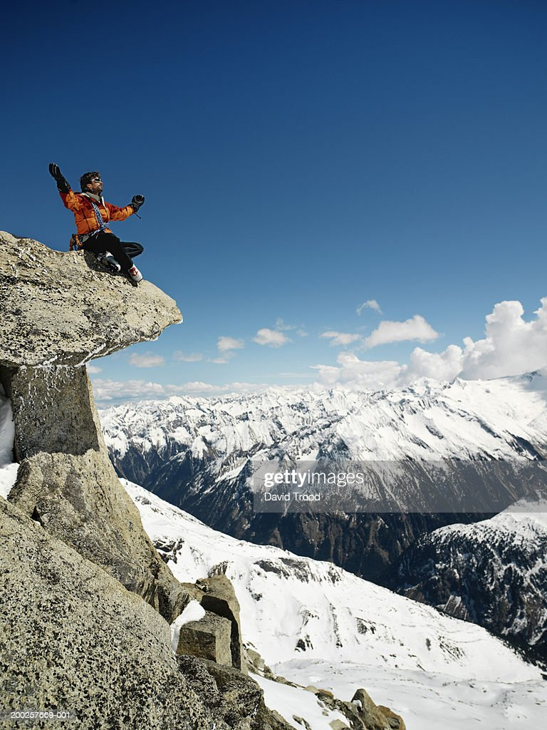 Male mountain climber meditating on overhanging rock, low angle view : Stock Photo
