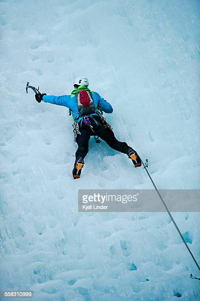 Male mountain climber on ice-covered rock face, lo