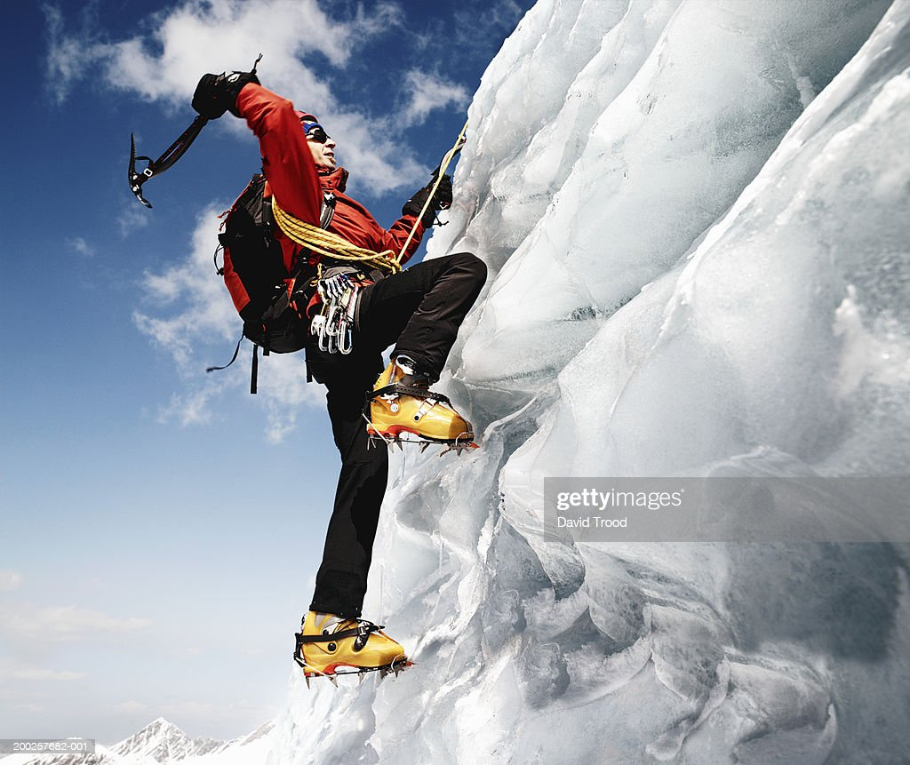 Male mountain climber on ice-covered rock face, low angle view : Stock Photo