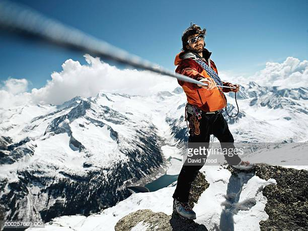 Male mountain climber pulling rope taut, portrait