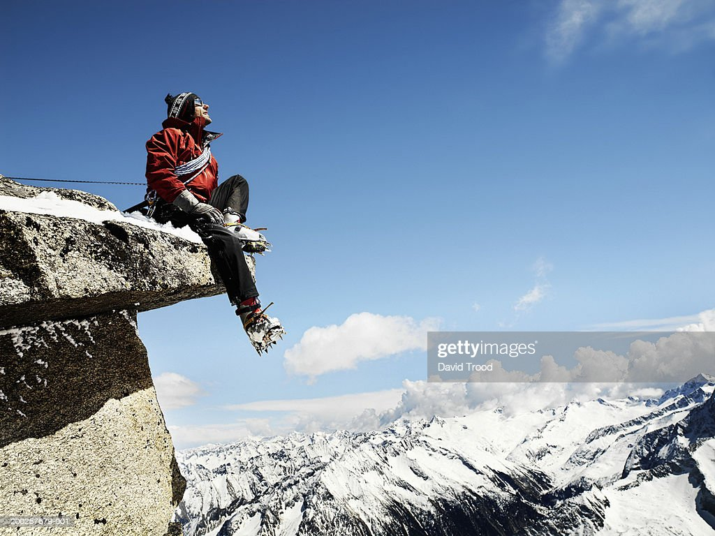 Male mountain climber sitting on overhanging rock, low angle view : Stock Photo