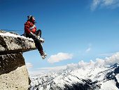 Male mountain climber sitting on overhanging rock, low angle view