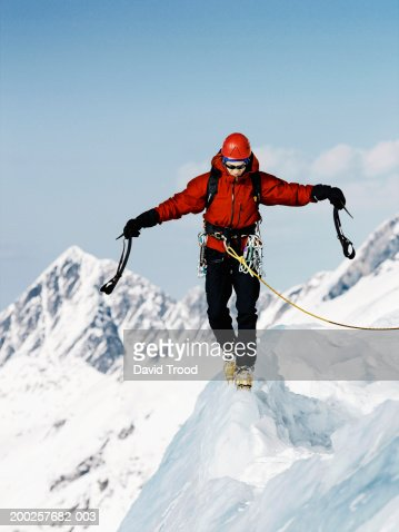 Male mountain climber walking along ridge, arms outstretched : Stock Photo