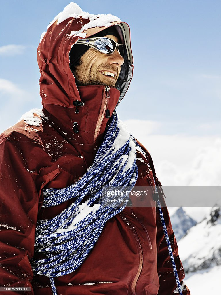 Male mountain climber wearing sunglasses, smiling, close-up : Stock Photo