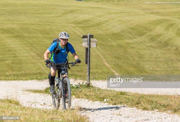 A male mountainbiker crossing uphill Dolomite pastures, Italy