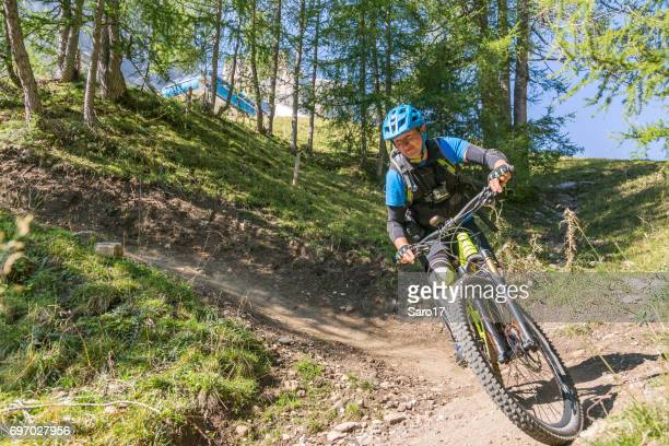Male mountainbiker is riding fast in hairpin turn in the Dolomites, Italy
