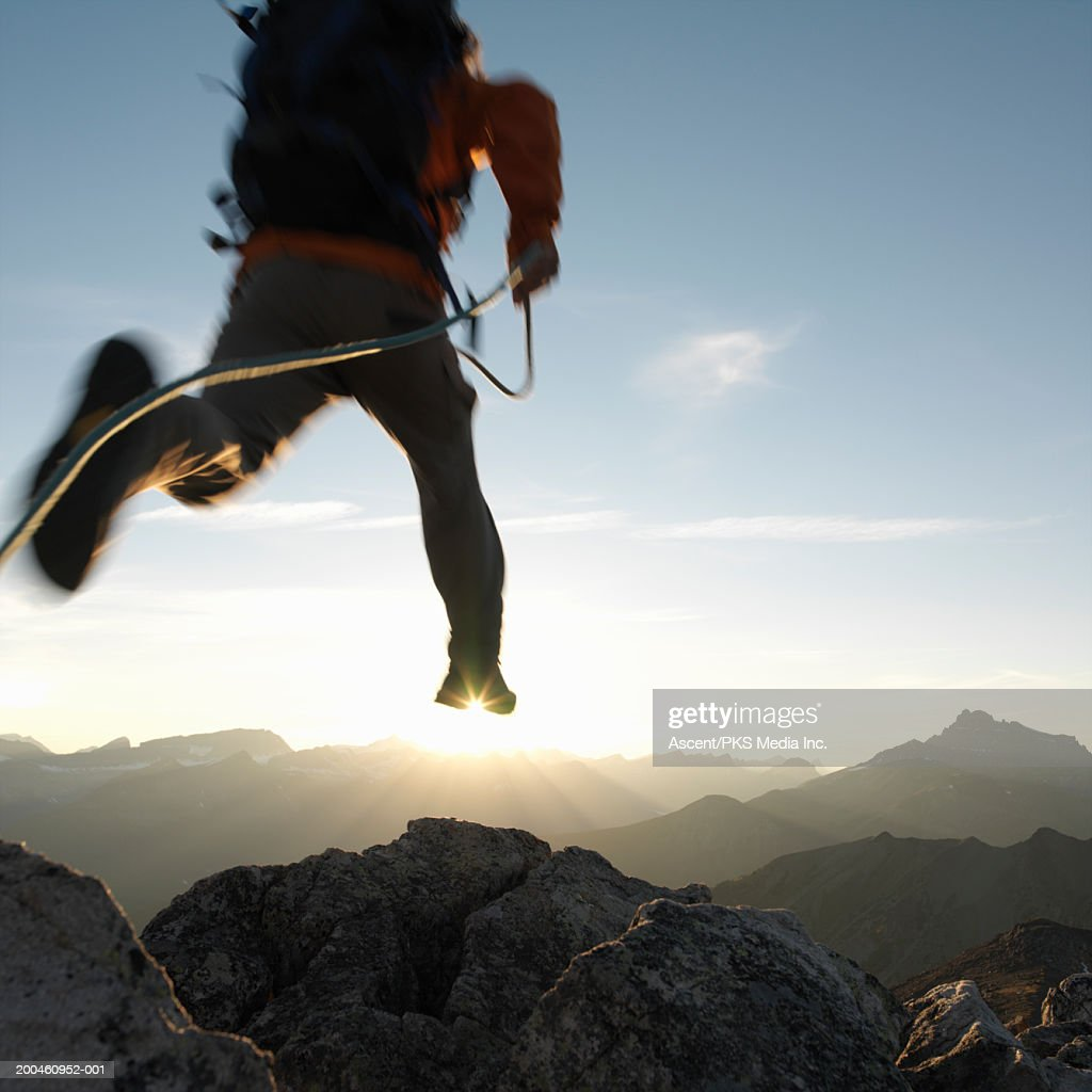 Male mountaineer leaping between rocks, low section, rear view, sunset : Stock Photo