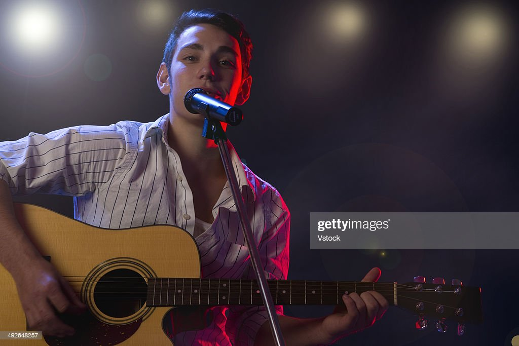 Male Musician Playing Guitar And Singing On Stage Stock ...