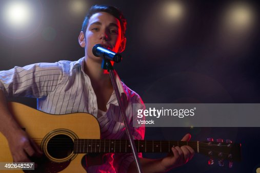 Male musician playing guitar and singing on stage