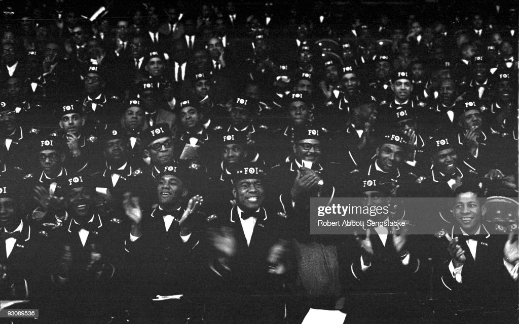 Male Nation of Islam attendees, many in the uniform of the Fruit of Islam, applaud as they attend Saviour's Day (held on February 26) celebrations, Chicago, Illinois, mid 1960s.
