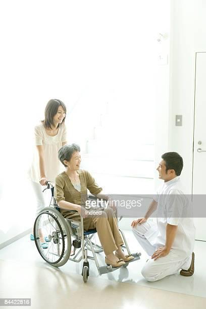 Male nurse kneeling to senior woman in wheel chair