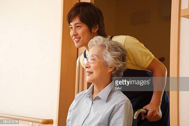 Male nurse pushing senior woman in wheelchair, smiling