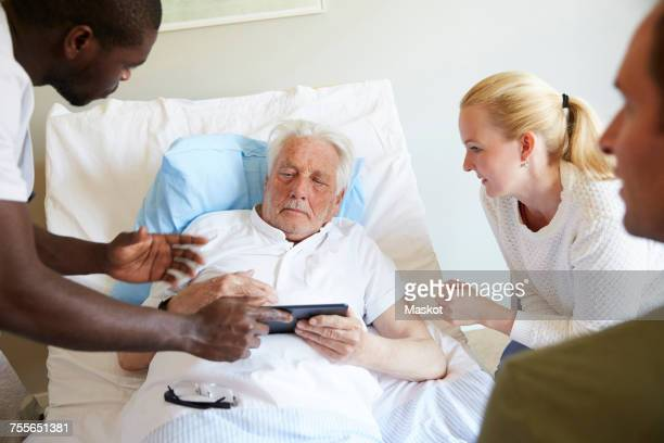 Male nurse showing digital tablet to senior man and couple at hospital ward