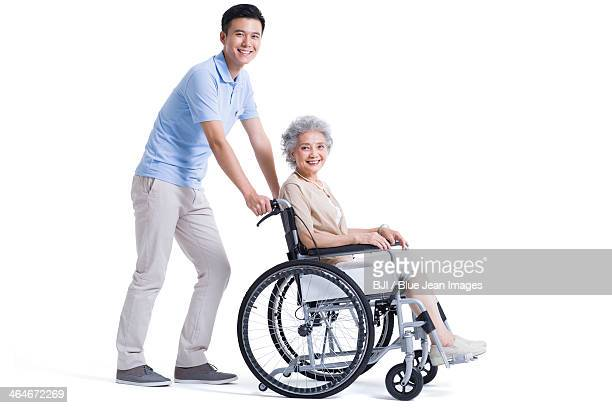 Male nursing assistant taking care of senior in wheelchair