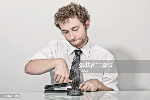 Male office employee stapling tie with stapler