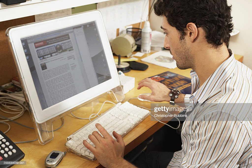 Male office worker at workstation, view over shoulder : Stock Photo