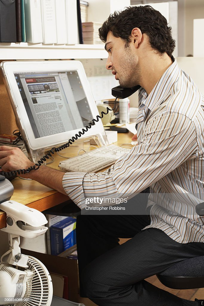 Male office worker balancing phone on shoulder, looking at computer : Stock Photo