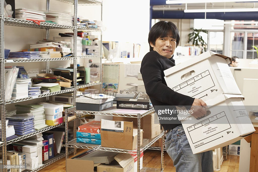 Male office worker carrying archive boxes, straining, portrait