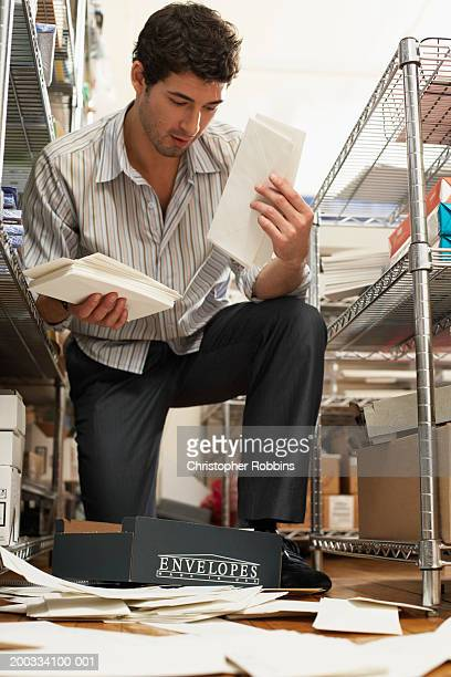 Male office worker gathering spilt envelopes by stationery shelving