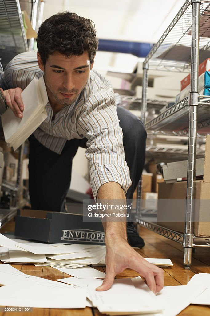 Male office worker gathering spilt envelopes by stationery shelving : Stock Photo