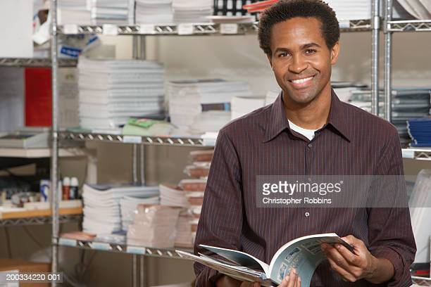 Male office worker holding open manual, smiling, portrait
