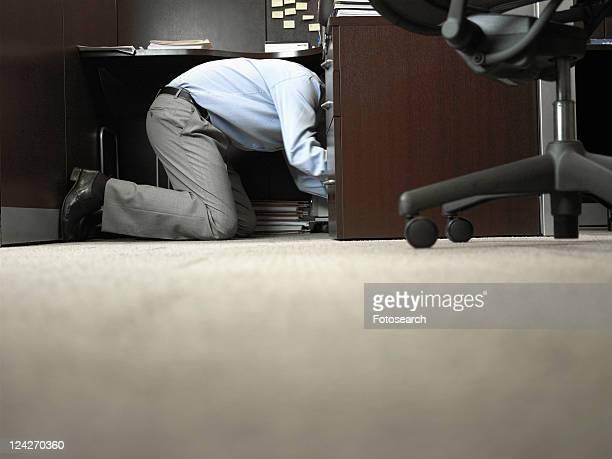 Male office worker kneeling under desk