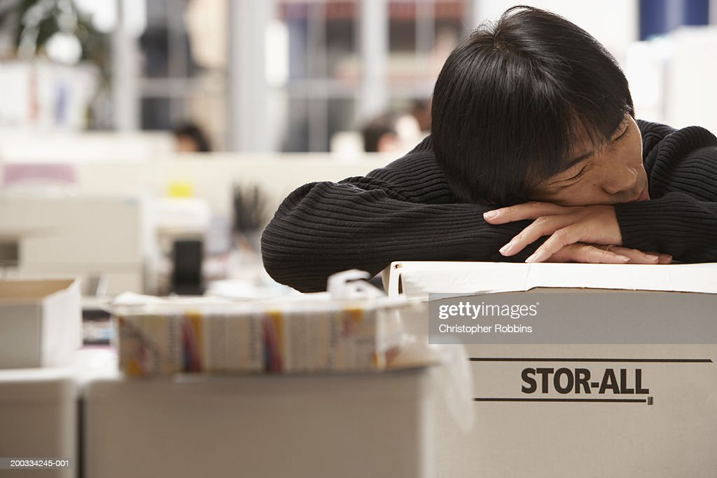 Male office worker leaning on boxes, eyes closed : Stock Photo