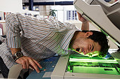 Male office worker photocopying side of face, mouth open, eyes closed