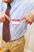 Male office worker pointing to name tag on shirt