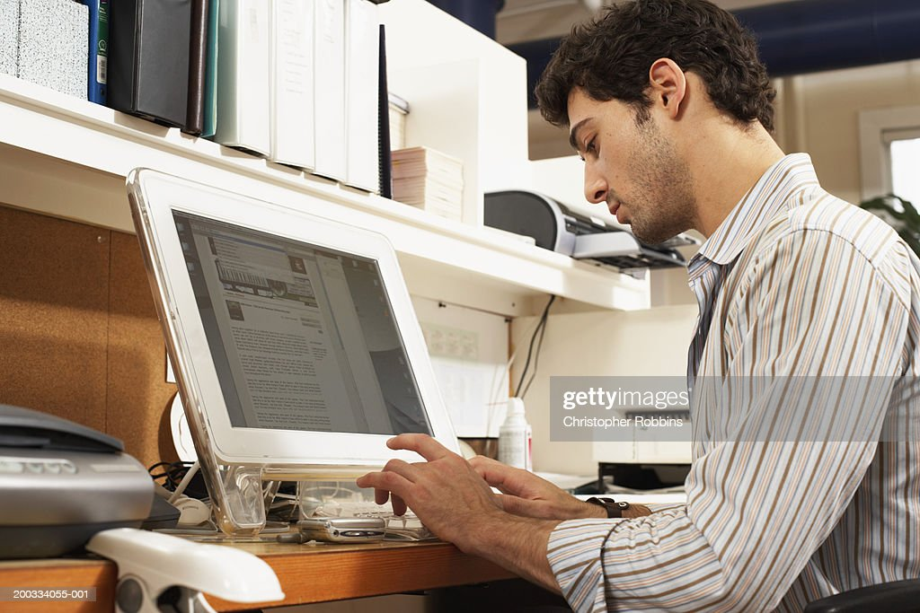 Male office worker sitting at workstation, typing : Stock Photo