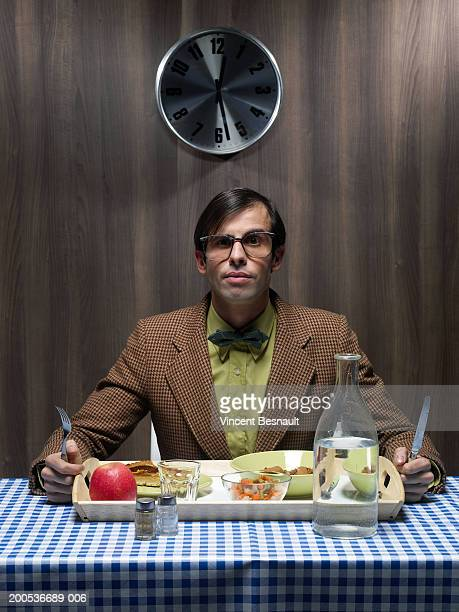 Male office worker sitting in canteen with lunch tray, portrait