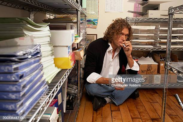 Male office worker sitting on floor of storage area, smoking cigarette