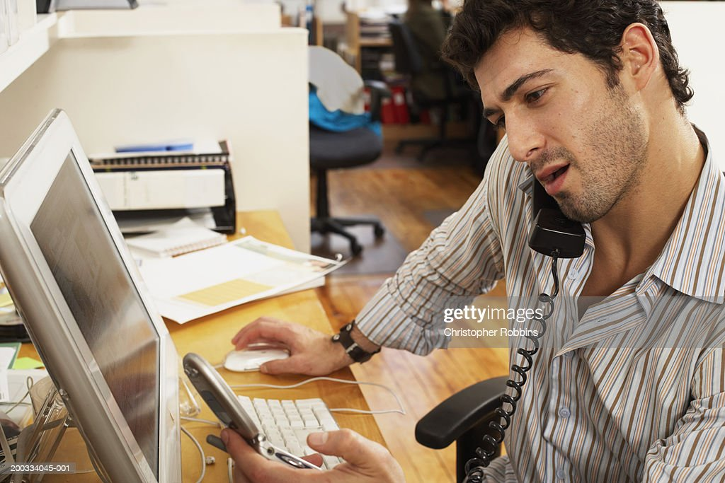 Male office worker using telephone, balancing handset against shoulder : Stock Photo