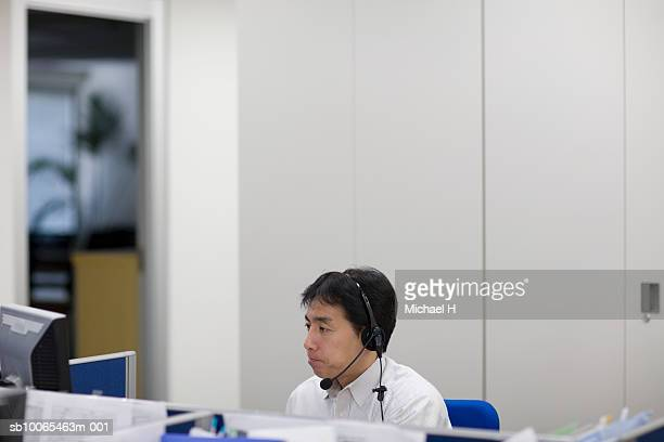 Male office worker with headset on desk