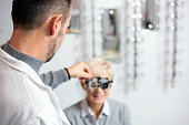 Male ophthalmologist examining mature woman at the ophthalmology clinic, determining diopter. Rear view over his shoulder. Healthcare and medicine concept