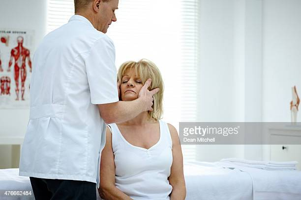 Male osteopath stretching a woman neck