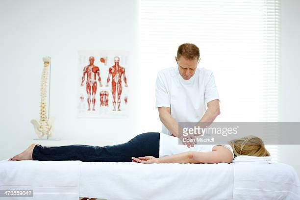 Male osteopath treating back problem of a woman