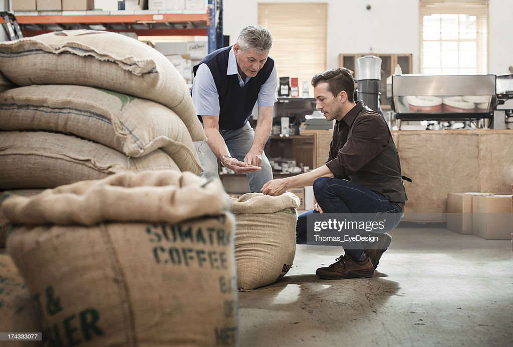 Male owner of a coffee roasting business talking with worker : Stock Photo