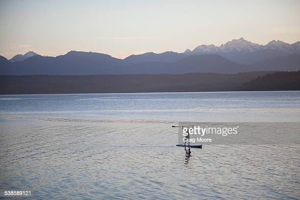 A male paddles his stand up paddle board on the Puget Sound near Poulsbo, Washington.