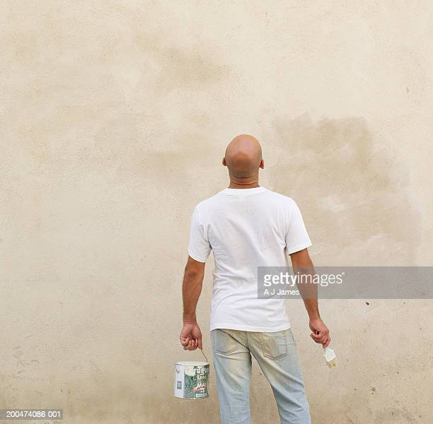 Male painter looking at wall, rear view